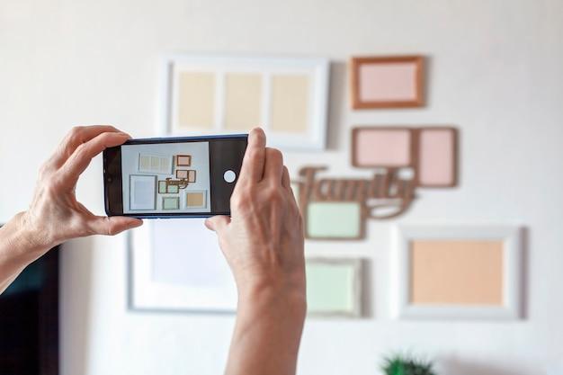 Женщина фотографирует белую стену с набором различных пустых вертикальных и горизонтальных рамок для картин, проект семейной фотогалереи, чтобы запечатлеть момент, шаблон макета на белой стене, образ жизни