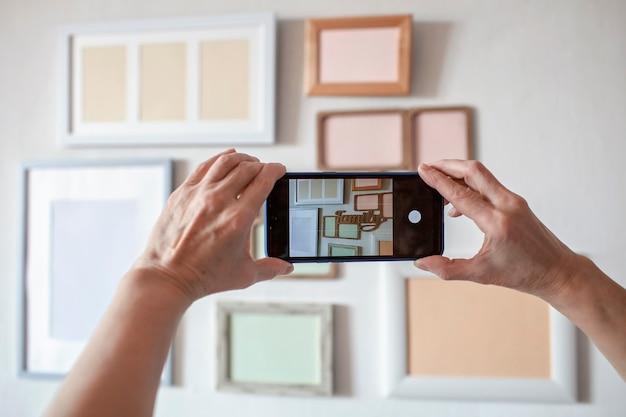 さまざまな空の垂直と水平の額縁のセットで白い壁の写真を作る女性、瞬間をキャプチャする家族写真ギャラリープロジェクト、白い壁のモックアップテンプレート、ライフスタイル