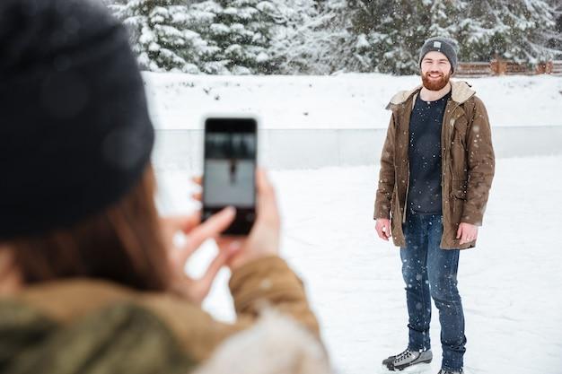 Женщина делает фото на смартфоне мужчины на открытом воздухе