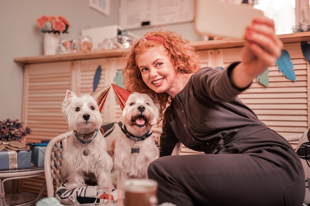 Женщина делает фото. рыжая красивая женщина улыбается, делая фото с именинными собаками