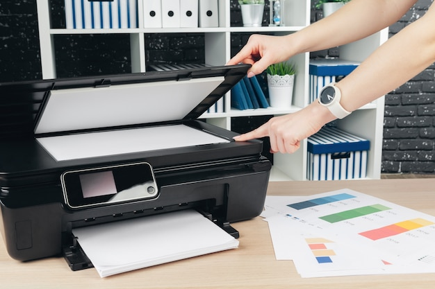 Woman making photocopy using copier in office