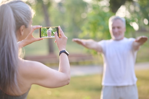 A woman making a picture of her husband while he exercising