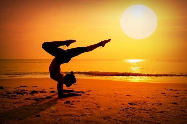 Женщина делает сосны на пляже на закате