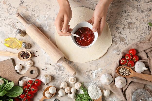 Женщина делает пиццу на светлой поверхности