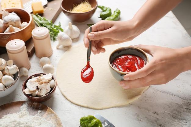 軽い表面でピザを作る女性