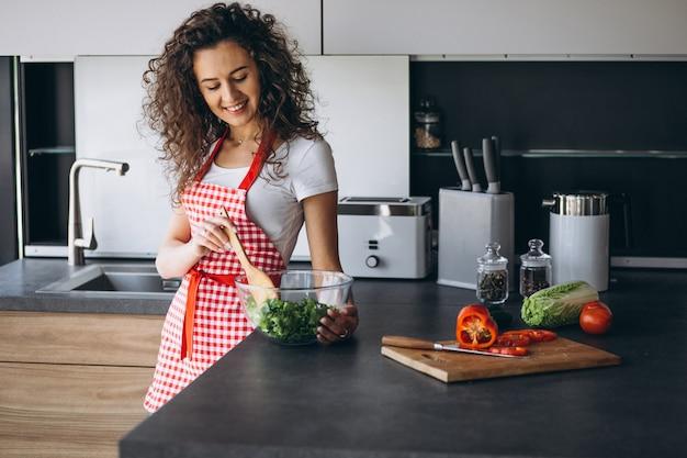 Женщина готовит салат на кухне