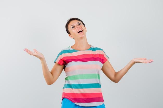 Женщина делает жест весов в полосатой футболке и выглядит счастливой.