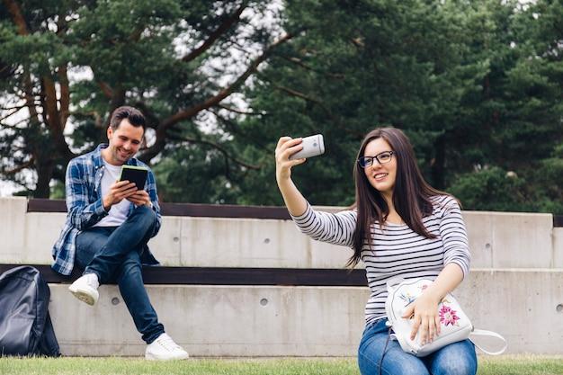 Donna che fa selfie e libro di lettura dell'uomo