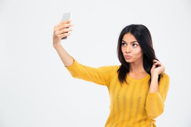 スマートフォンで自分撮り写真を作る女性