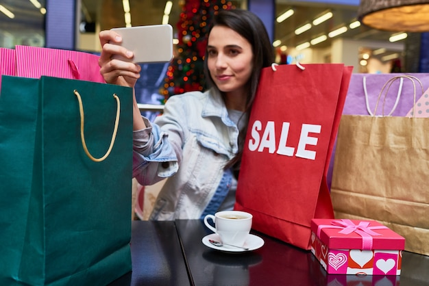 Woman making selfie portrait after shopping
