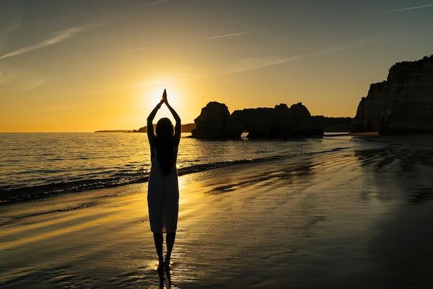 Женщина делает shilouette руками и солнцем на закате на пляже