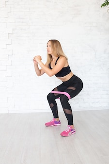 Woman making squats with elastic band