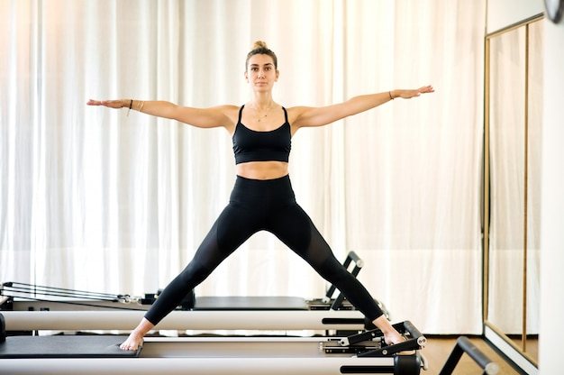 Woman making standing yoga pilates exercise