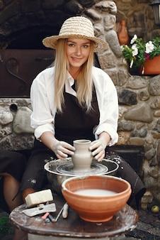 Donna che fa un vaso con argilla