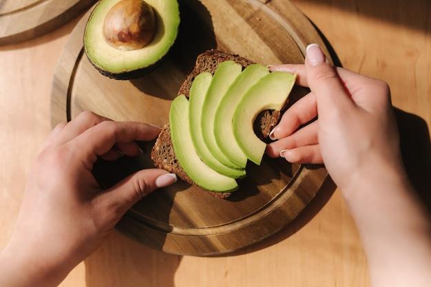 Женщина делает веганский бутерброд с ржаным хлебом, авокадо и кунжутом. женщина положила авокадо на ржаной хлеб
