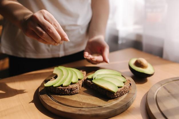 Женщина делает веганский бутерброд с ржаным хлебом, авокадо и кунжутом. женщина посыпает кунжутом