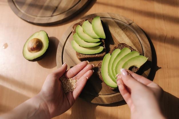 Женщина делает веганский бутерброд с ржаным тостом, авокадо и кунжутом. женщина посыпает