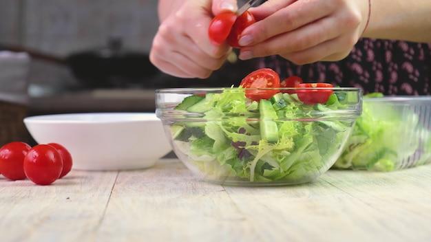 野菜サラダを作る女性。セレクティブフォーカス。自然。