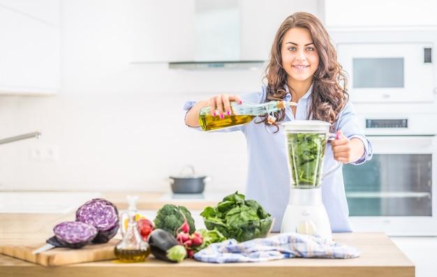 부엌에서 믹서기로 야채 수프나 스무디를 만드는 여자. 건강한 음식을 준비하거나 올리브 오일과 신선한 야채를 곁들인 음료를 준비하는 젊은 행복한 여성.