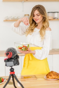 Woman making vegetables salad on camera