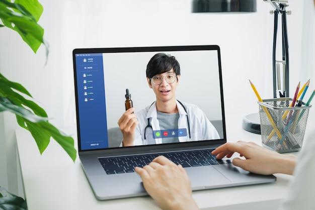 ノートパソコンで医師にビデオ通話をし、オンラインカウンセリングのヘルプを提供する女性。