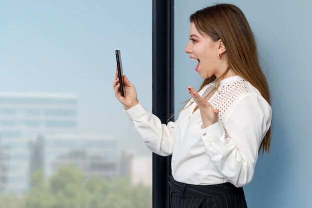 그녀의 휴대 전화로 영상 통화를 하는 여자 집에서 일하는 개념