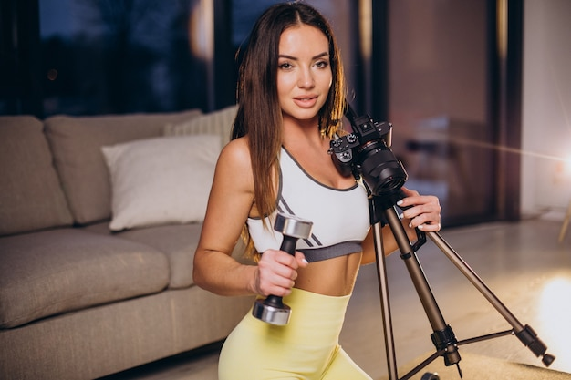 Woman making video of workout at home