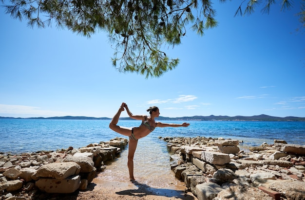 Женщина делает позу йоги возле морской воды