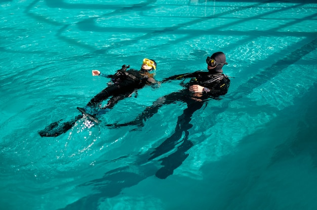 Woman and male divemaster, lesson in diving school