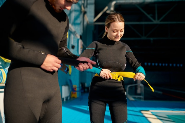 Woman and male instructor tries on scuba gear, diving school. teaching people to swim underwater, indoor swimming pool interior on background