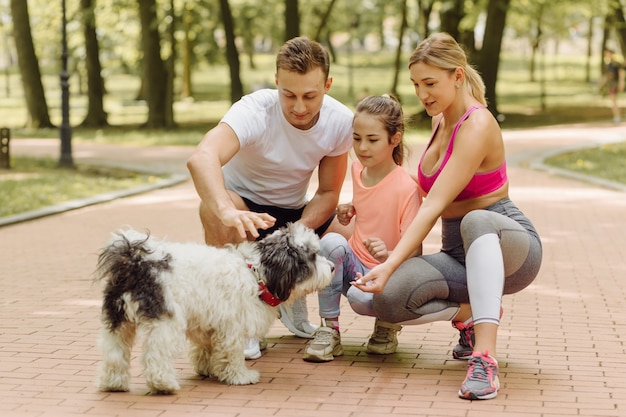 여자, 남자, 어린 소녀는 공원에서 개와 함께 산책을 간다