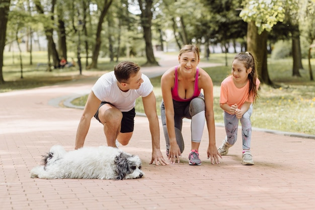 女性、男性、少女が公園で犬と一緒に走りに行く