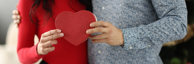 Woman and man are holding box with gift in form of heart in hands