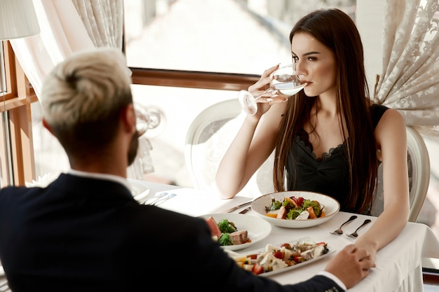 Woman and a man are holding hands on a romantic date at the restaurant