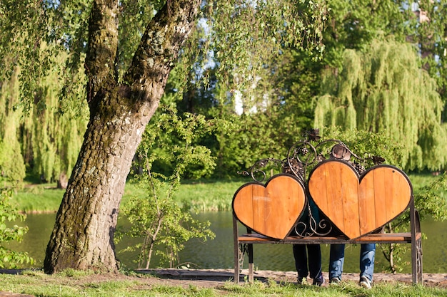 Woman and man are sitting on a bench with two big hearts under