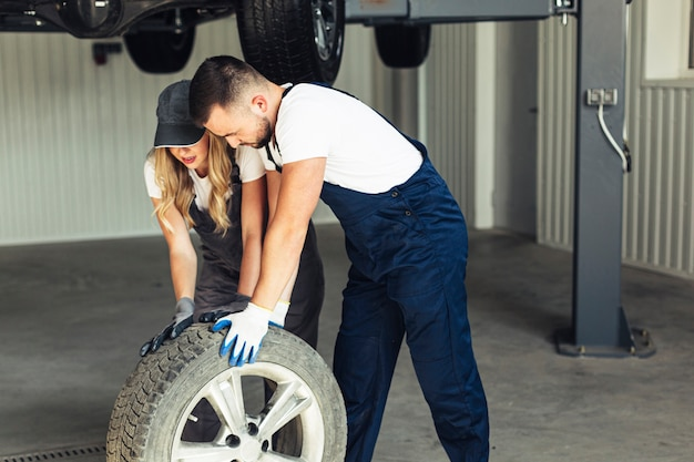Woman and man at auto service changing wheels