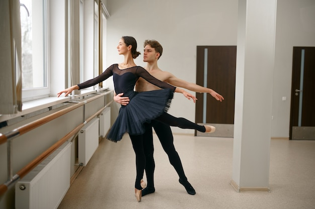 Woman and man ballet dancers dancing at barre