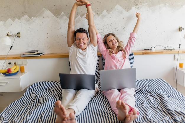 Woman and man in bed in morning smiling happy working online, family living together in bedroom wearing pajamas