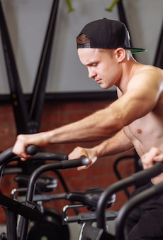 Woman and man biking in gym, exercising legs doing cardio workout cycling bikes