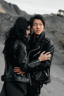 Woman and man in black clothes outdoors. asiatics.