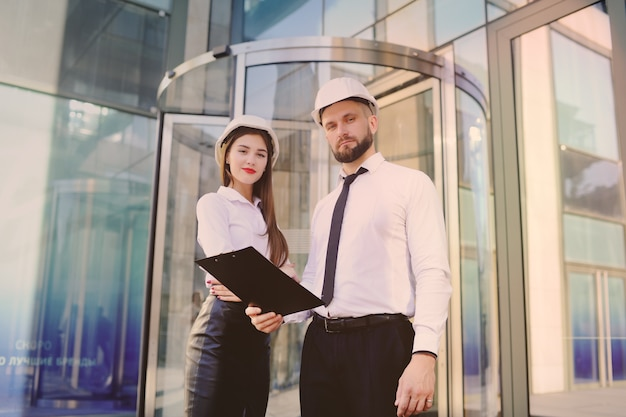 A woman and a man in business clothes and in white construction helmets discuss a construction plan or a contract signature