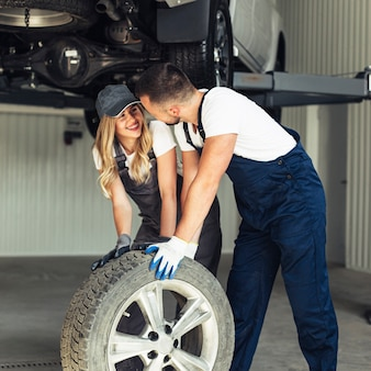 Woman and man changing car wheel together