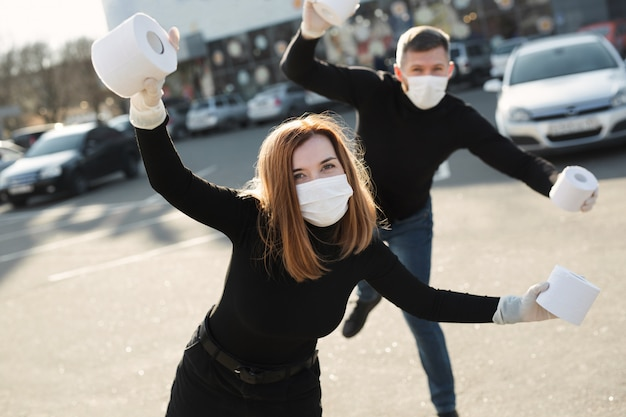 A woman and a man in a coronavirus face mask hold large rolls of toilet paper on a city street and indulge