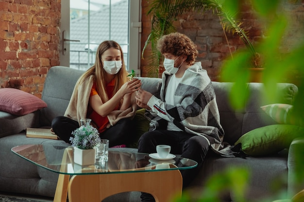 Woman and man, couple in protective masks and gloves isolated at home with coronavirus respiratory symptoms such as fever, headache, cough. healthcare, medicine, quarantine, treatment concept.