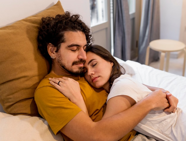 Woman and man cuddling in bed