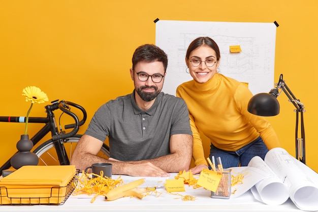 Woman and man developers create architect project use blueprints sketches look happily, after successful working day have productive cooperation
