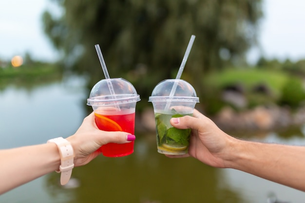 Woman and man during the walk holds in hands a fresh drink