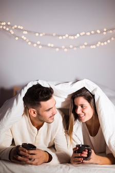 Woman and man in duvet with mugs lying on bed in room