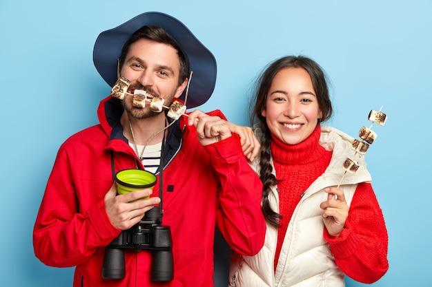 Donna e uomo mangiano marshmallow arrostiti fatti sul fuoco da campeggio, fanno un picnic nella foresta, godono del tempo libero, bevono bevande calde, indossano abiti casual, posano contro il muro blu