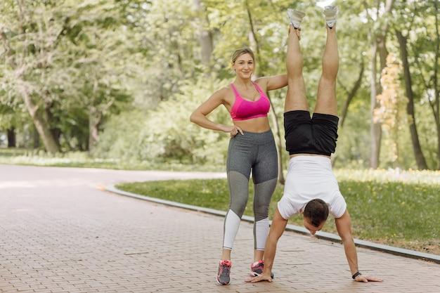 La donna e l'uomo fanno esercizi all'aperto. uomo in piedi sulle sue mani